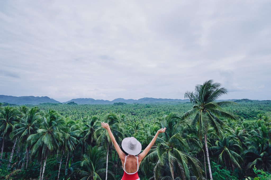 Young woman in hat on tropical vacation